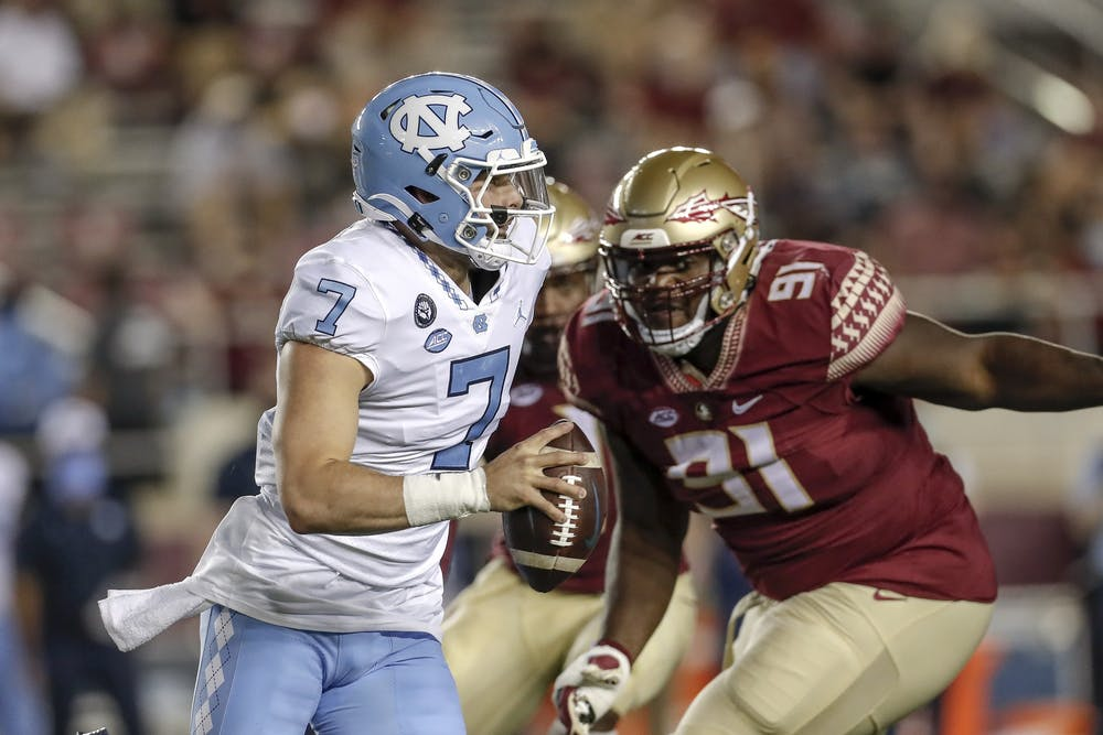 UNC Quarterback Sam Howell (7)  is forced out the pocket by FSU defensive tackle Robert Cooper (91)  during the game at Doak Campbell Stadium on Bobby Bowden Field on October 17, 2020 in Tallahassee, Florida. Photo by Don Juan Moore/Character Lines via the ACC.