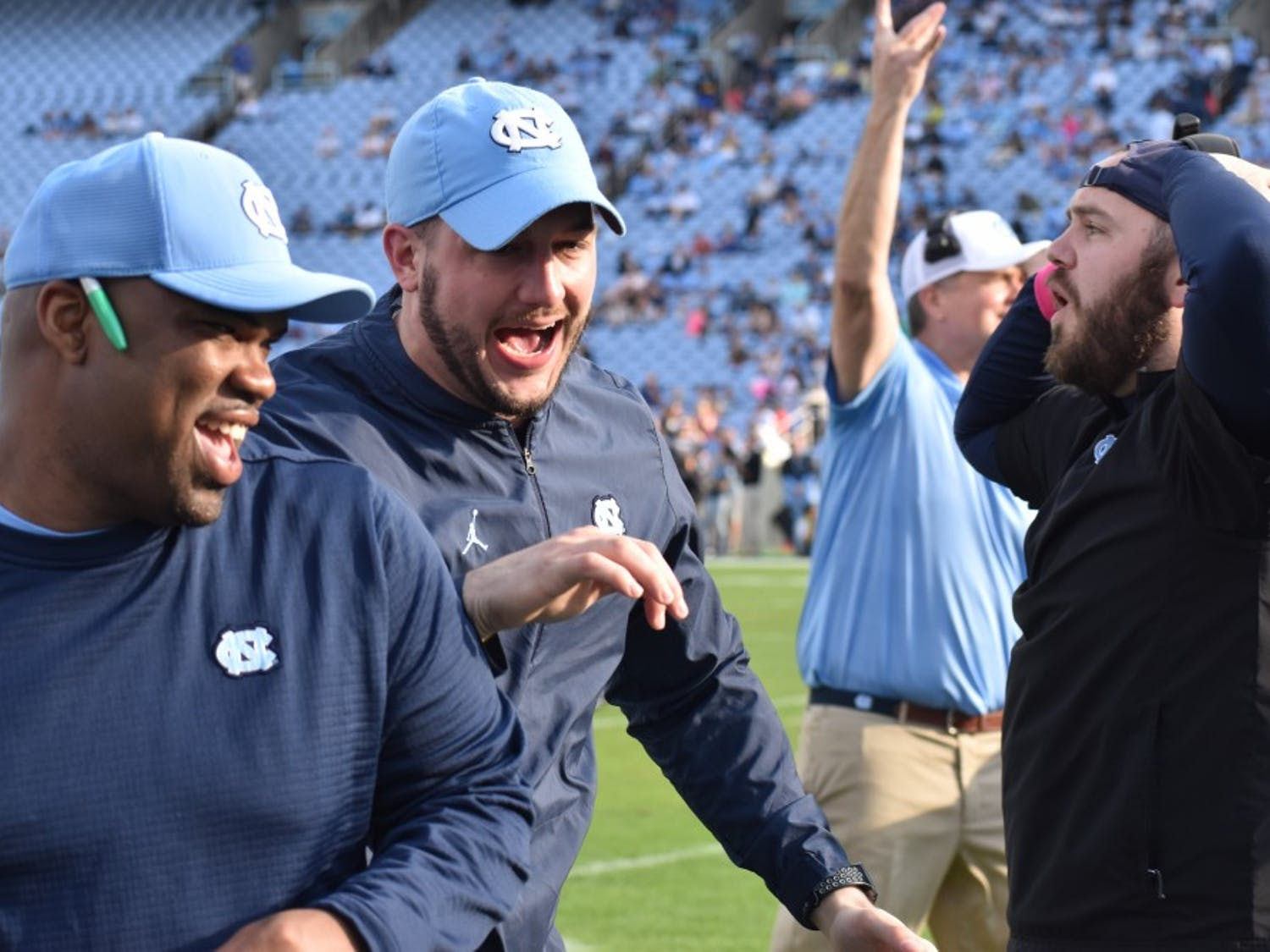 Two UNC football staff members celebrate and one expresses disappointment as the defense team scored a touchdown following a fumble by first-year running back Devon Lawrence (3) and first-year defensive back Storm Duck (29) sprinted 44 yards to the end zone in the Spring Football Game on April 13, 2019 in Kenan Stadium. The Carolina team defeated the Tar Heel team 25-10
