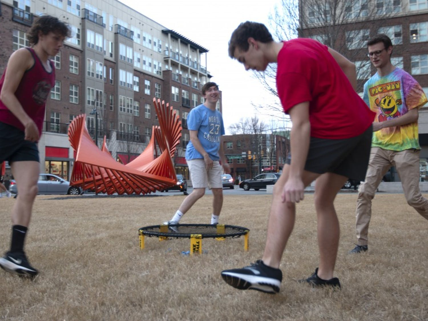 """(From left) First-years Russell Engle, Max Sherrill, Nick Belk and Bennett Stillerman play Spikeball in front of a sculpture outside of Granville Towers on Tuesday, Feb. 5, 2019. The steel installation, titled """"Going Through"""" and designed by Robert Winkler, stands as one of several public art displays in the Town of Chapel Hill."""
