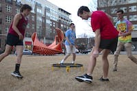 "(From left) First-years Russell Engle, Max Sherrill, Nick Belk and Bennett Stillerman play Spikeball in front of a sculpture outside of Granville Towers on Tuesday, Feb. 5, 2019. The steel installation, titled ""Going Through"" and designed by Robert Winkler, stands as one of several public art displays in the Town of Chapel Hill."