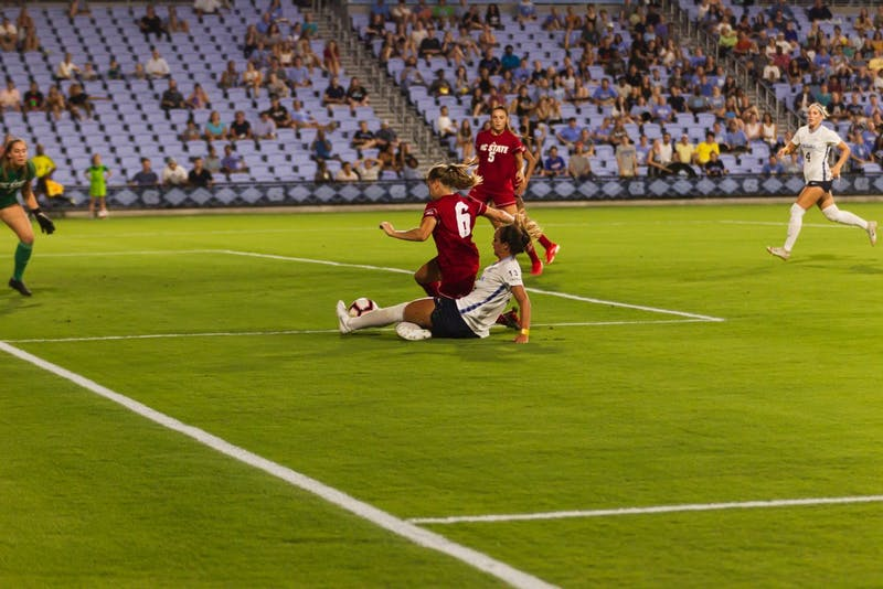 UNC freshman forward Isabel Cox (13)  makes a slide tackle for the ball, stealing from NC State redshirt sophomore defender Lulu Guttenberger (6) in the UNC Soccer and Lacrosse Stadium on Thursday, Sept. 26, 2019.