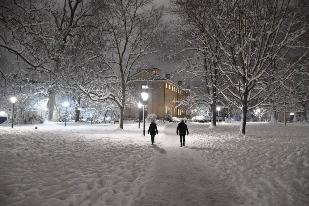 <p>People walk through snowy North Campus on a Wednesday night in 2018.</p>