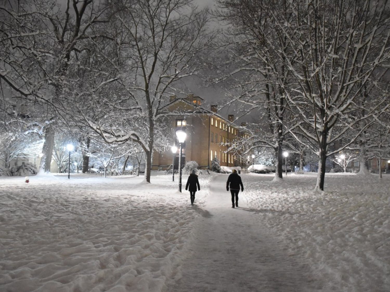 People walk through snowy North Campus on a Wednesday night in 2018.