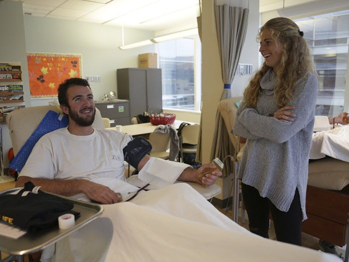 Tommy Bancroft (left), a long snapper on UNC-CH's football team, donates platelets and talks with Emma Bozek (right), a midfielder and forward on the field hockey team. Bozek is one of five students who organized the event.