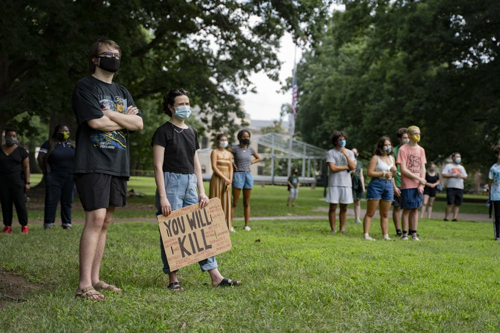 <p>Students and other UNC community members in masks listen to Jennifer Standish, a UNC graduate student in the Department of History, speak at the Die-In Protest organized by the Anti-Racist Graduate Worker Collective on Wednesday, Aug. 5, 2020. The protest called for UNC to transition to fully remote classes for the Fall 2020 semester after a letter of caution sent to Chancellor Guskiewicz by the Orange County Health Director Quintana Stewart.</p>