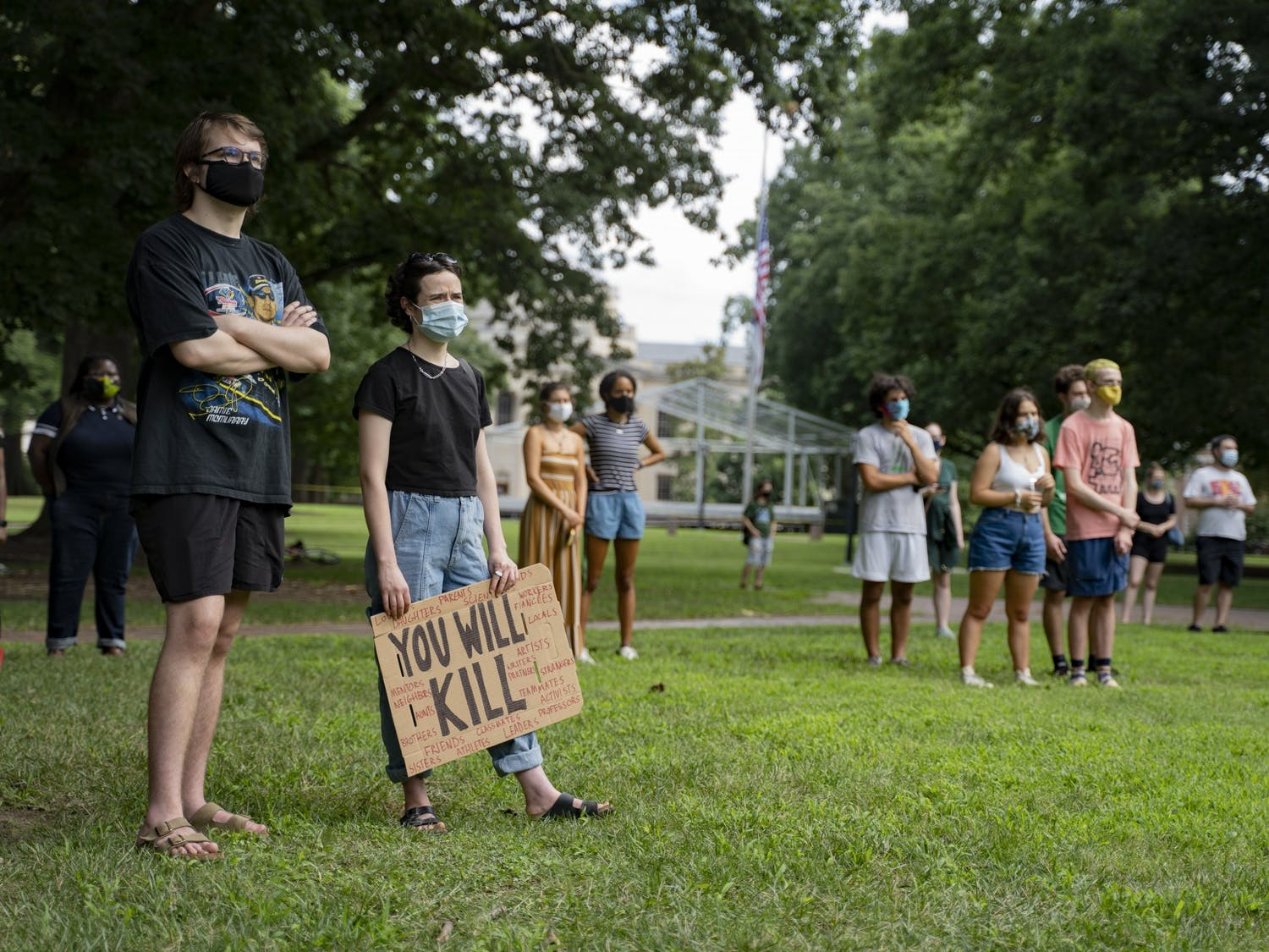 Students and other UNC community members in masks listen to Jennifer Standish, a UNC graduate student in the Department of History, speak at the Die-In Protest organized by the Anti-Racist Graduate Worker Collective on Wednesday, Aug. 5, 2020. The protest called for UNC to transition to fully remote classes for the Fall 2020 semester after a letter of caution sent to Chancellor Guskiewicz by the Orange County Health Director Quintana Stewart.