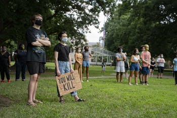 Students and other UNC community members in masks listen to Jennifer Standish, a UNC graduate student in the Department of History, speak at the Die-In Protest on Wednesday, Aug. 5, 2020. The protest called for UNC to transition to fully remote classes for the Fall 2020 semester after a letter of caution sent to Chancellor Guskiewicz by the Orange County Health Director Quintana Stewart.
