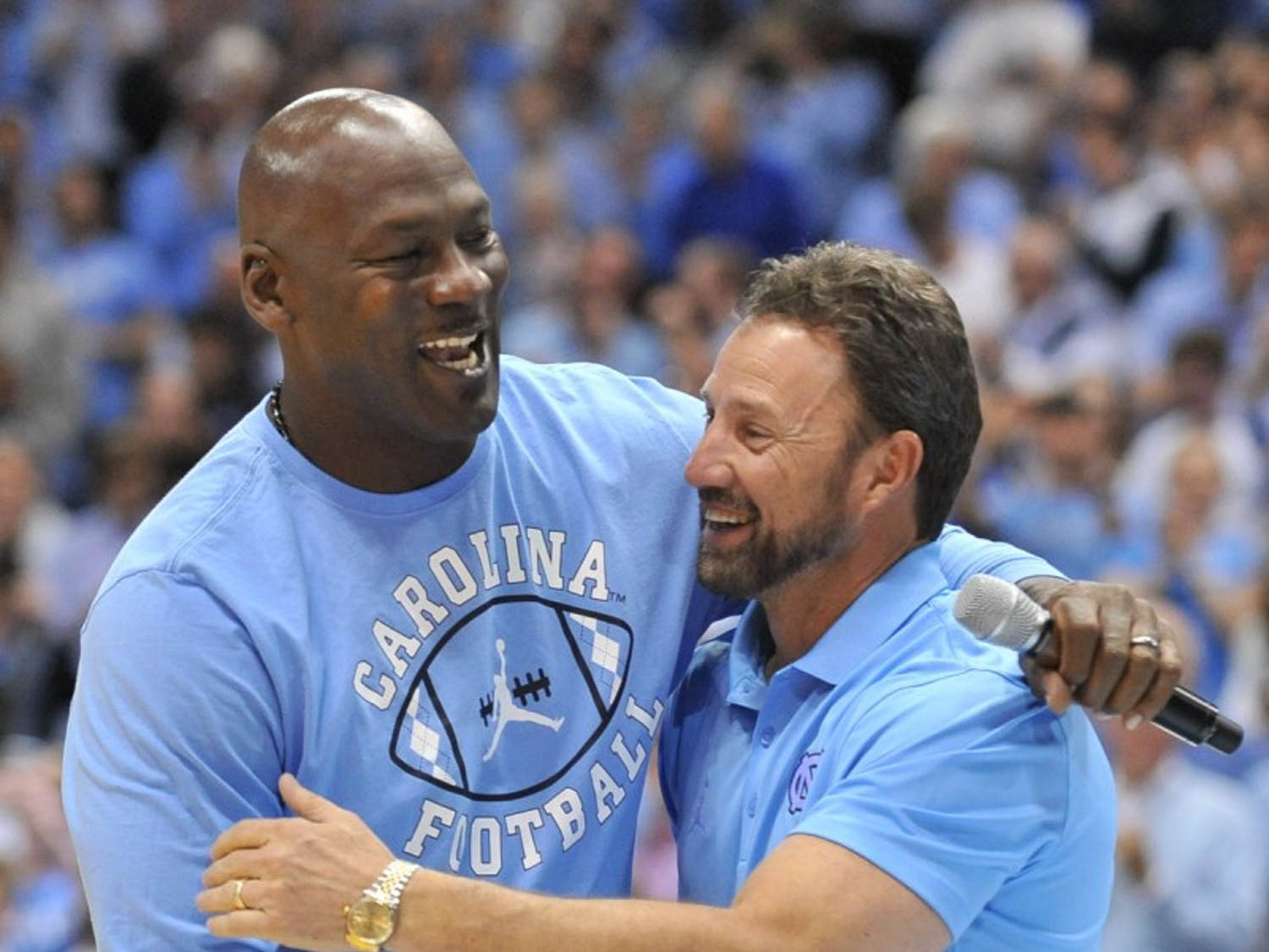 Former North Carolina basketball player and NBA Hall of Fame inductee Michael Jordan shakes hand with North Carolina football coach Larry Fedora at halftime of Saturday night's game. Jordan made an appearance to announce a new partnership between the Jordan brand and the NorthCarolina football team starting in the 2017 season.