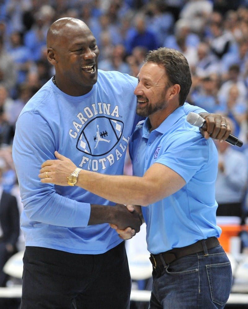 Former North Carolina basketball player and NBA Hall of Fame inductee Michael Jordan shakes hand with North Carolina football coach Larry Fedora at halftime of Saturday night's game. Jordan made an appearance to announce a new partnership between the Jordan brand and the North Carolina football team starting in the 2017 season.