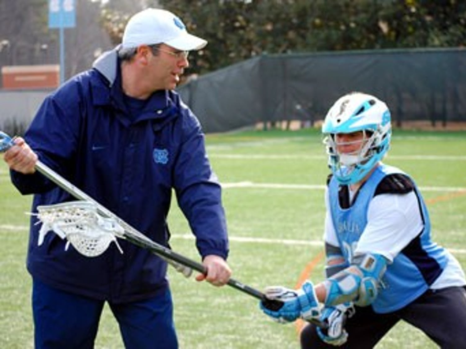 """Lacrosse coach Joe Breschi"""" in his first year at UNC works with freshman Thomas Wood after practice. Breschi and the team started the season 6-0."""