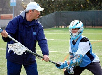 "Lacrosse coach Joe Breschi"" in his first year at UNC works with freshman Thomas Wood after practice. Breschi and the team started the season 6-0."
