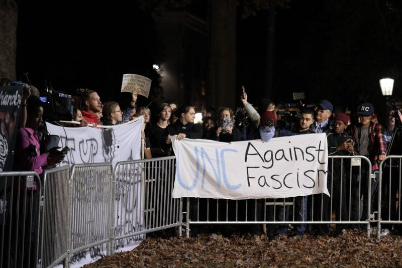 Demonstrators gather around the site of Silent Sam after Carol Folt and the Board of Trustees announced a proposal to place the monument in a new historic center on campus on Monday, Dec. 3, 2018.