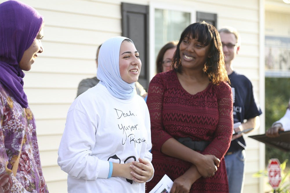 """Sana Ansari (left), (from Cary, N.C., who recently graduated from UNC), represented """"OurThreeWinners.org"""" and Doha Hindi (right of Ansari), a junior at NC State, spoke in honor of Deah, Yusor and Razan at the Habitat for Humanity's dedication ceremony on Tuesday. Habitat for Humanity dedicated Petrina McCoy's home to Deah Barakat, Yusor Abu-Salha, and Razan Abu-Salah, the three Muslim students who were killed in February."""