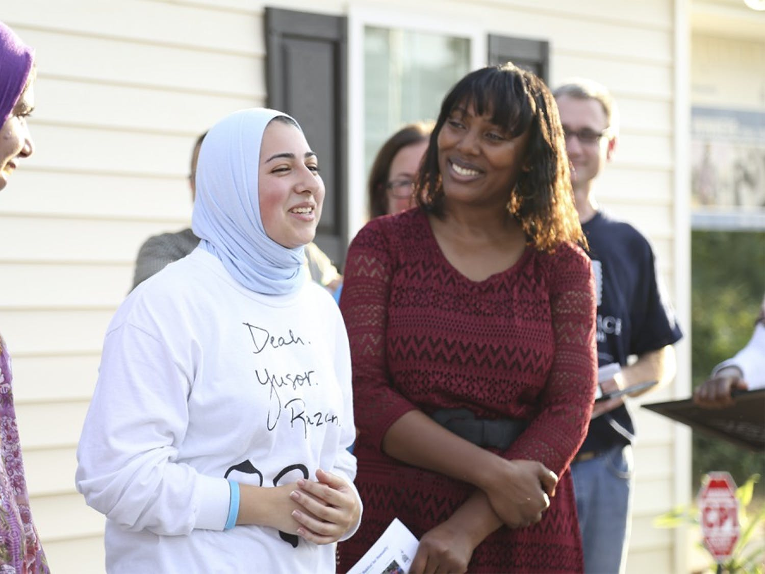 "Sana Ansari (left), (from Cary, N.C., who recently graduated from UNC), represented ""OurThreeWinners.org"" and Doha Hindi (right of Ansari), a junior at NC State, spoke in honor of Deah, Yusor and Razan at the Habitat for Humanity's dedication ceremony on Tuesday. 