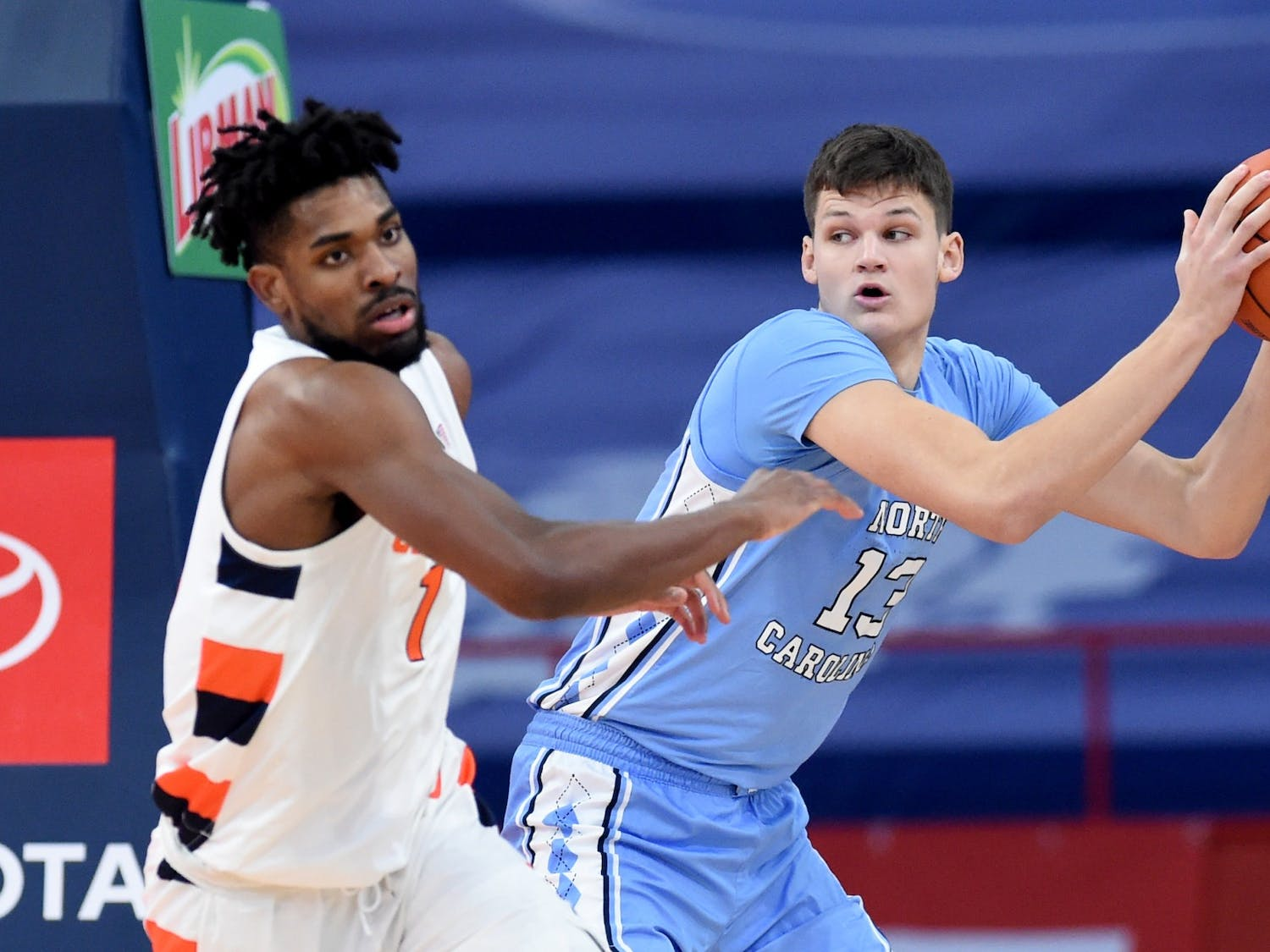 North Carolina Tar Heels forward Walker Kessler (13) pulls down a rebound in front of Syracuse Orange forward Quincy Guerrier (1) in a game between Syracuse and North Carolina  at the Carrier Dome in Syracuse N.Y. March 1, 2021. Photo by Dennis Nett for Syracuse Athletics.