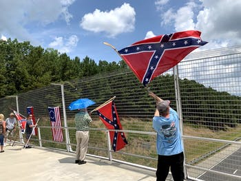 Demonstrators wave confederate flags over the American Tobacco Trail I-40 Pedestrian Bridge in Durham on Sunday, July 7.