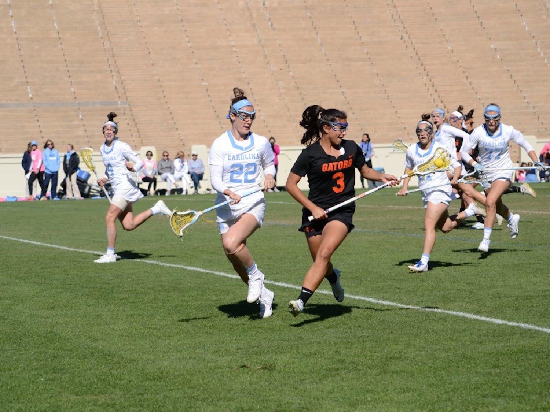 Midfielder Maggie Bill (22) plays defense against Florida during the women's lacrosse game on Saturday in Kenan Stadium.