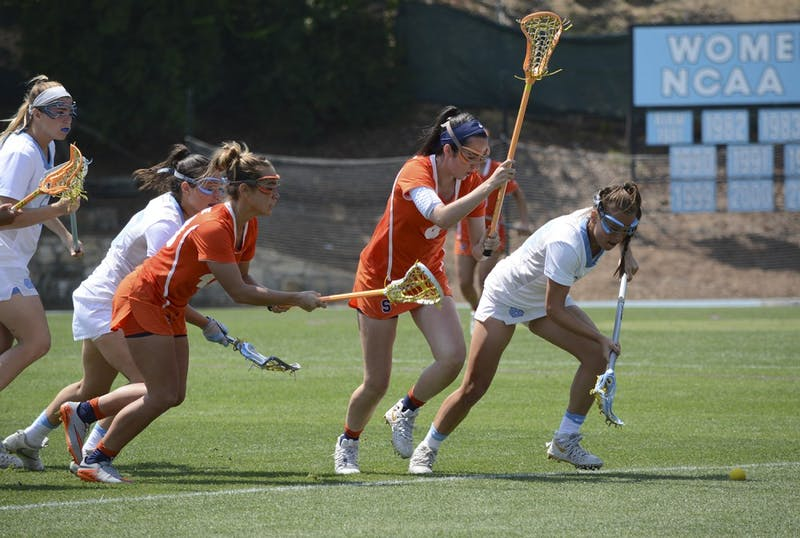 Midfielder Catie Woodruff (34) chases after the ball while being chased by Syracuse defenders.