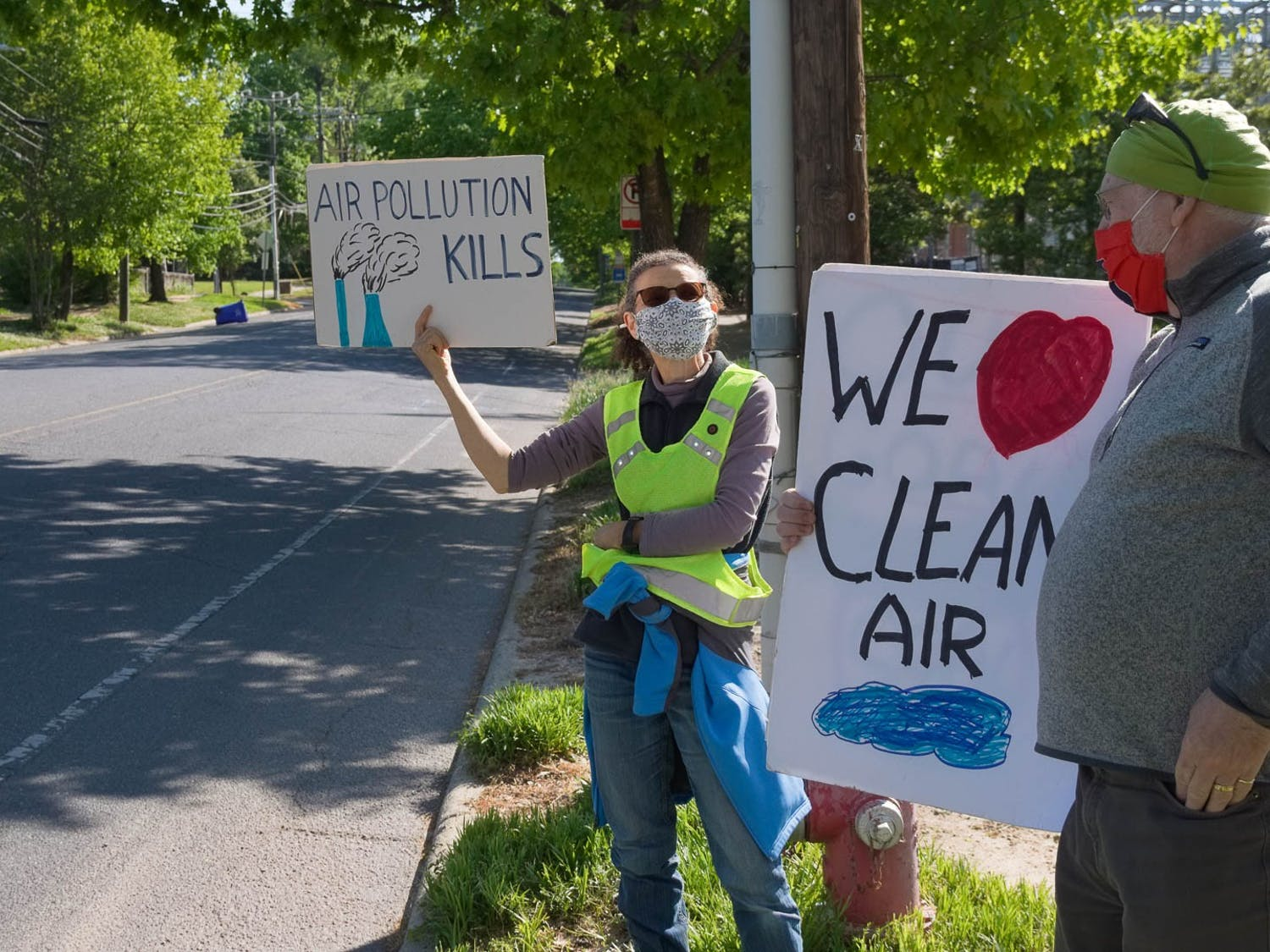 Catherine Lavau and Gary Richards hold up signs outside of UNC's coal plant on Friday, Apr. 23, 2021.