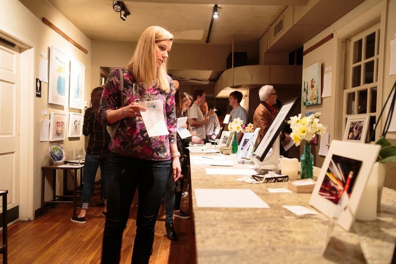 Sarah Yarbrough looks at a table of art at the Mixed Concrete Art Auction on Saturday night at Tru.