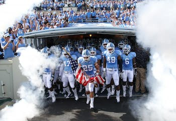 Matt Merletti, a redshirt junior safety, leads UNC out of the tunnel with the flag his brother Mike gave him from his military stationing in Afghanistan.