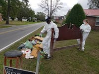 (From left to right) Community member from Lumberton and Jessica Aldous carry debris out of a victim's house. (Photo courtesy of Michelle He)