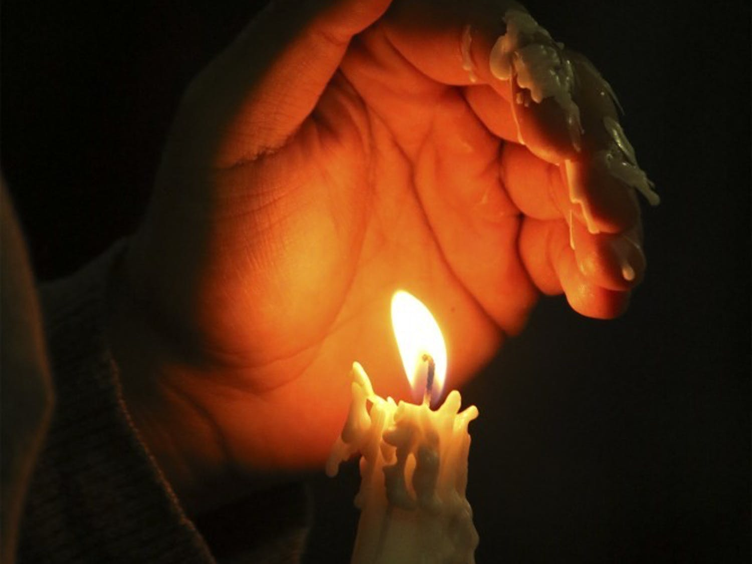 Student holds candle at a vigil in 2016.