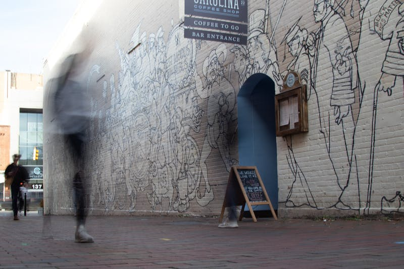 People walk by Parade, a mural by local artist Michael Brown on the outside wall of Carolina Coffee Shop on Thursday, Jan. 9, 2020.