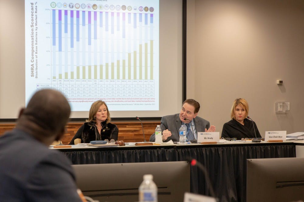 Vice-Chair Kellie Hunt Blue (right) and Chair Wendy Floyd Murphy (left) listen as Committee Member Matt Brody (center) presents aspects of a survey which collected data on arears of university faculty pay, retention, and participation across the UNC system and Historically Minority-serving institutions. Thursday, Jan. 24, 2019 at the UNC Center for School Leadership Development.