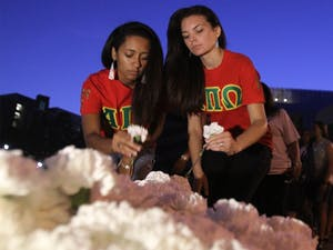 From left, Taylor Springs of the NC State chapter of the Native American Sorority Alpha Pi Omega and Brooke Spaulding of the Campbell chapter pick up carnations for the silent walk held for the anniversary of Faith Hedgepeth's death on Saturday, Sept. 7, 2013.