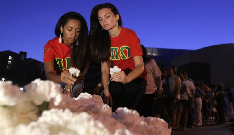 From left, Taylor Springs of the NC State chapter of the Native American Sorority Alpha Pi Omega and Brooke Spaulding of the Campbell chapter pick up carnations for the silent walk held for the anniversary of Faith Hedgepeth's death on Saturday.