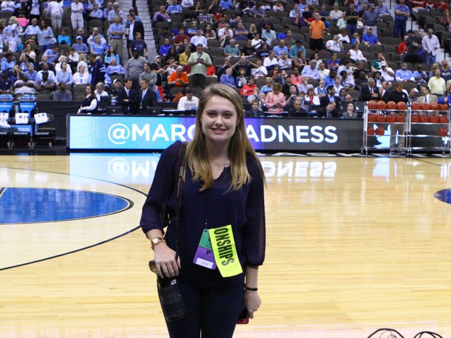 The Daily Tar Heel senior photographer Halle Sinnott stands on the court during half time of Thursday's game.