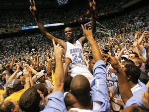 North Carolina's Marvin Williams (24) rides a wave of jubilant, powder blue-clad fans after UNC's 75-73 win against Duke on Sunday, March 6, 2005. William's put-back and free throw gave the Tar Heels the winning margin with 17 seconds left.