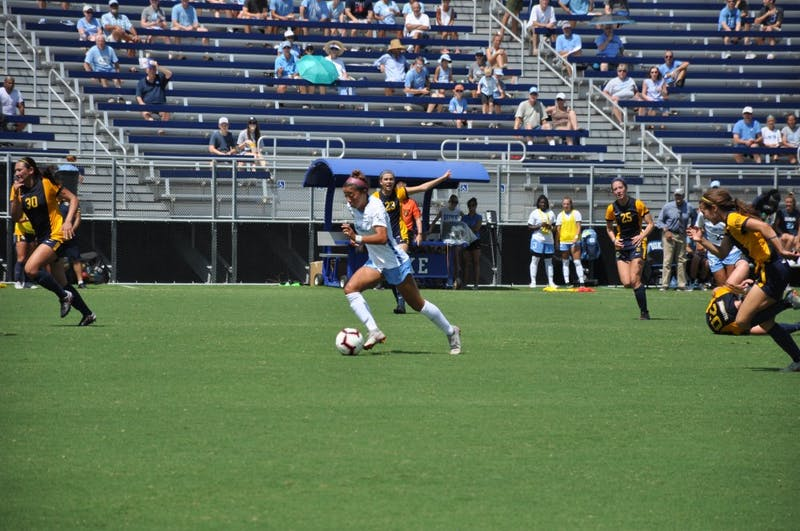 Forward (15) Zoe Redei dribbles down the field during Sunday's game at Koskinen Stadium.