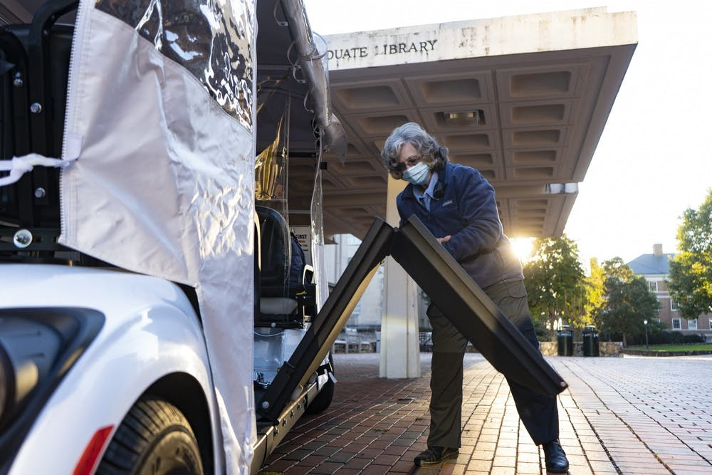 Ruth Confer, a point-to-point driver, opens up the wheelchair ramp on her car on Monday, Nov. 2, 2020. Confer works under UNC to help people with disabilities or injuries move around campus, but since COVID-19 started, she has only had two students use her assistance.