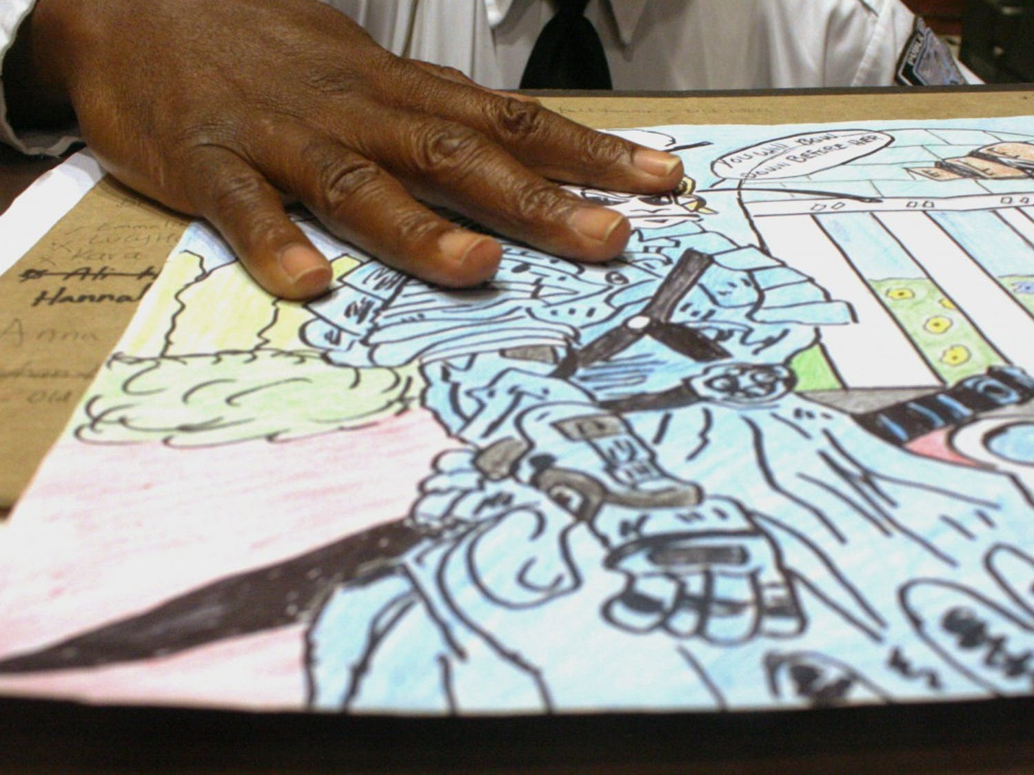 Moore holds a sketch of Rameses, the UNC mascot, wearing a Samurai outfit.