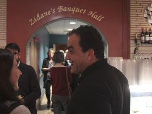 Mediterranean Deli owner Jamil Kadoura laughs with a guest at the dinner and silent auction event in support of Syrian refugees.