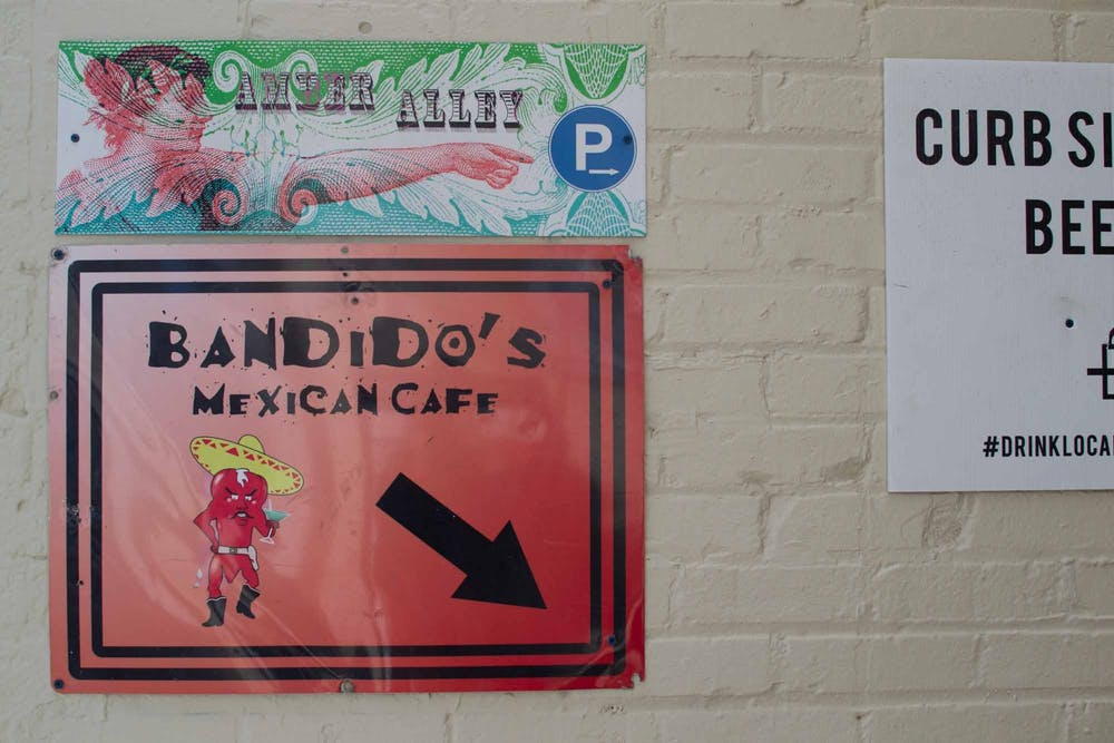 <p>A sign on Franklin Street directs pedestrians down to Bandidos Mexican Cafe on Feb. 4, 2021. After struggling with financial stress created by the COVID-19 pandemic, Chapel Hill restaurant Bandido's started a GoFundMe campaign last month to supplement its lull in foot traffic.&nbsp;</p>