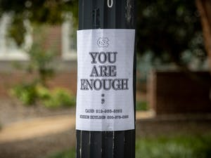 A sign listing numbers for the suicide hotline and CAPS is posted on a light pole outside of Murphey Hall on Oct. 11.