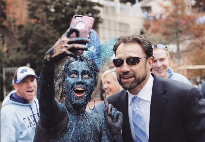 Alex Koszeghy, better known as Glitter Girl, takes a selfie with North Carolina football head coach Larry Fedora. Photo courtesy of Alexa Blaze.