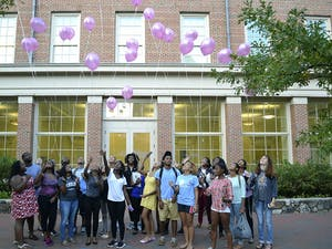 """Members of the Black Student Movement release balloons in honor of Breast Cancer Awareness month Wednesday afternoon in the SASB courtyard.  Members wrote message such as """"stay strong"""" and """"just keep fighting"""" on the balloons to be released in the sky."""