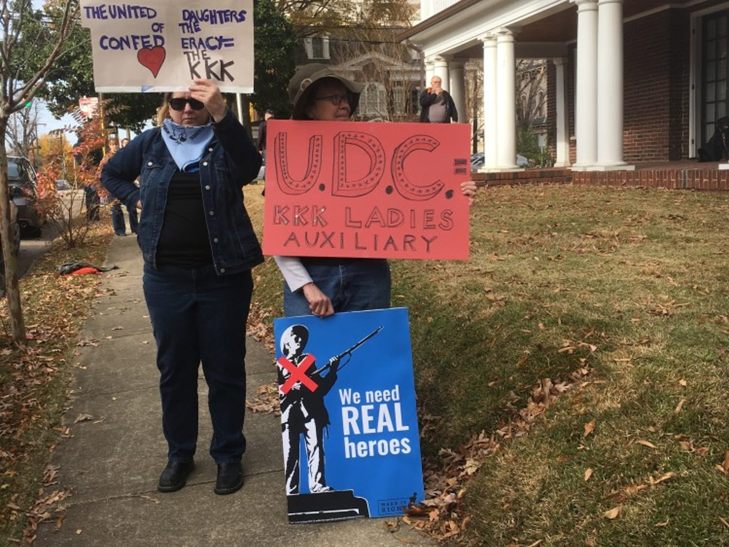 Two activists with Hillsborough Progressives Taking Action, including UNC professor Altha Cravey, protest a United Daughters of the Confederacy meeting.