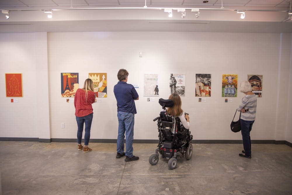 <p>The 2014 and 2015 winners of the Banned Books art competition inspire awe in several visitors to the installation currently being hosted on 109 E. Franklin St. on Monday, September 16, 2019. &nbsp;The exhibit features different artists's expressions of famous banned books in a gallery put together by Chapel Hill Public Library in honor of Banned Books Week.&nbsp;</p>