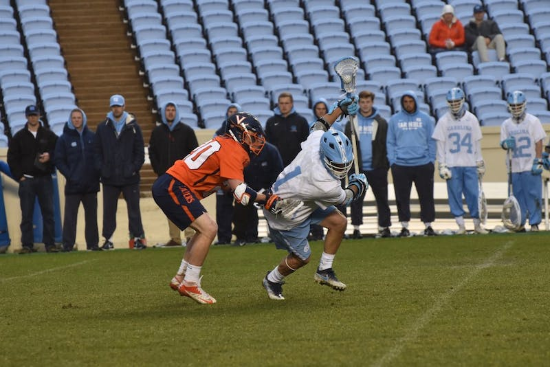 First-year Alex Trippi (1) fights past a Virginia defender on April 7 in Kenan Stadium.