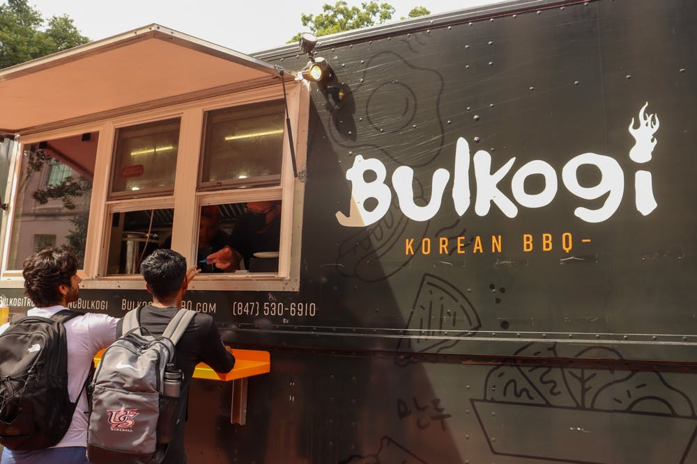 <p>Junior sports administration major TJ Nanugonda and junior computer science major Garv Srivastava exchange conversation with Bulkogi BBQ truck workers while paying for their food with their meal swipes.</p>
