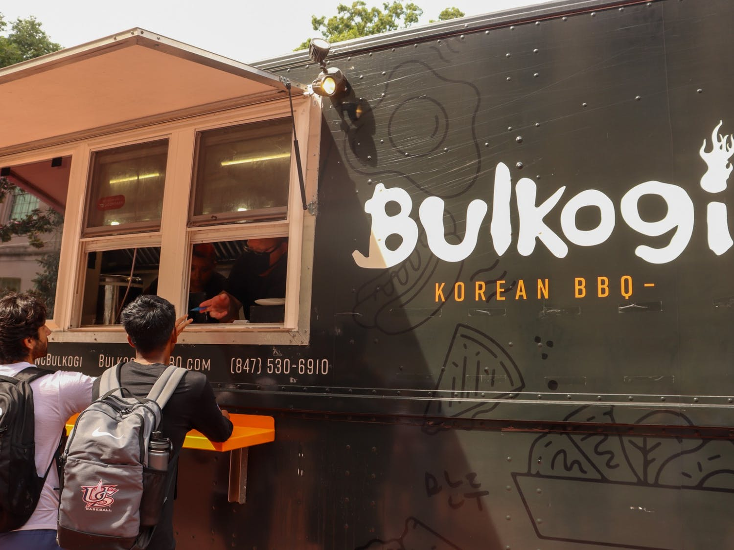 Junior sports administration major TJ Nanugonda and junior computer science major Garv Srivastava exchange conversation with Bulkogi BBQ truck workers while paying for their food with their meal swipes.
