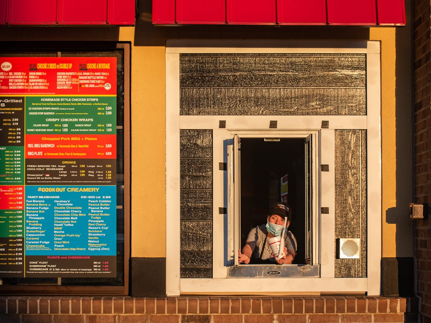 A Cookout employee hands a milkshake through the walk-up window of the Cookout in Wilkesboro, NC.