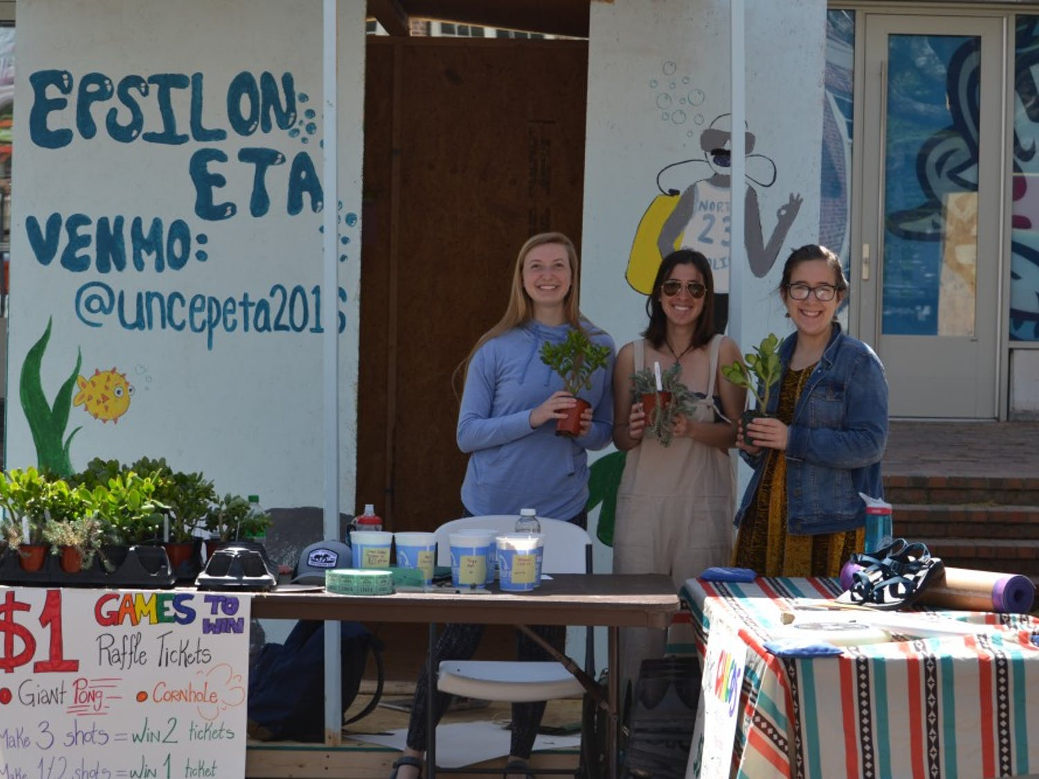 UNC students (from left to right) Emma Karlok, Allie Omens, and Elinor Solnick host the Epsilon ETA shack. Epsilon ETA raffled off various outdoor gear and sold succulents to raise money for Habitat for Humanity.