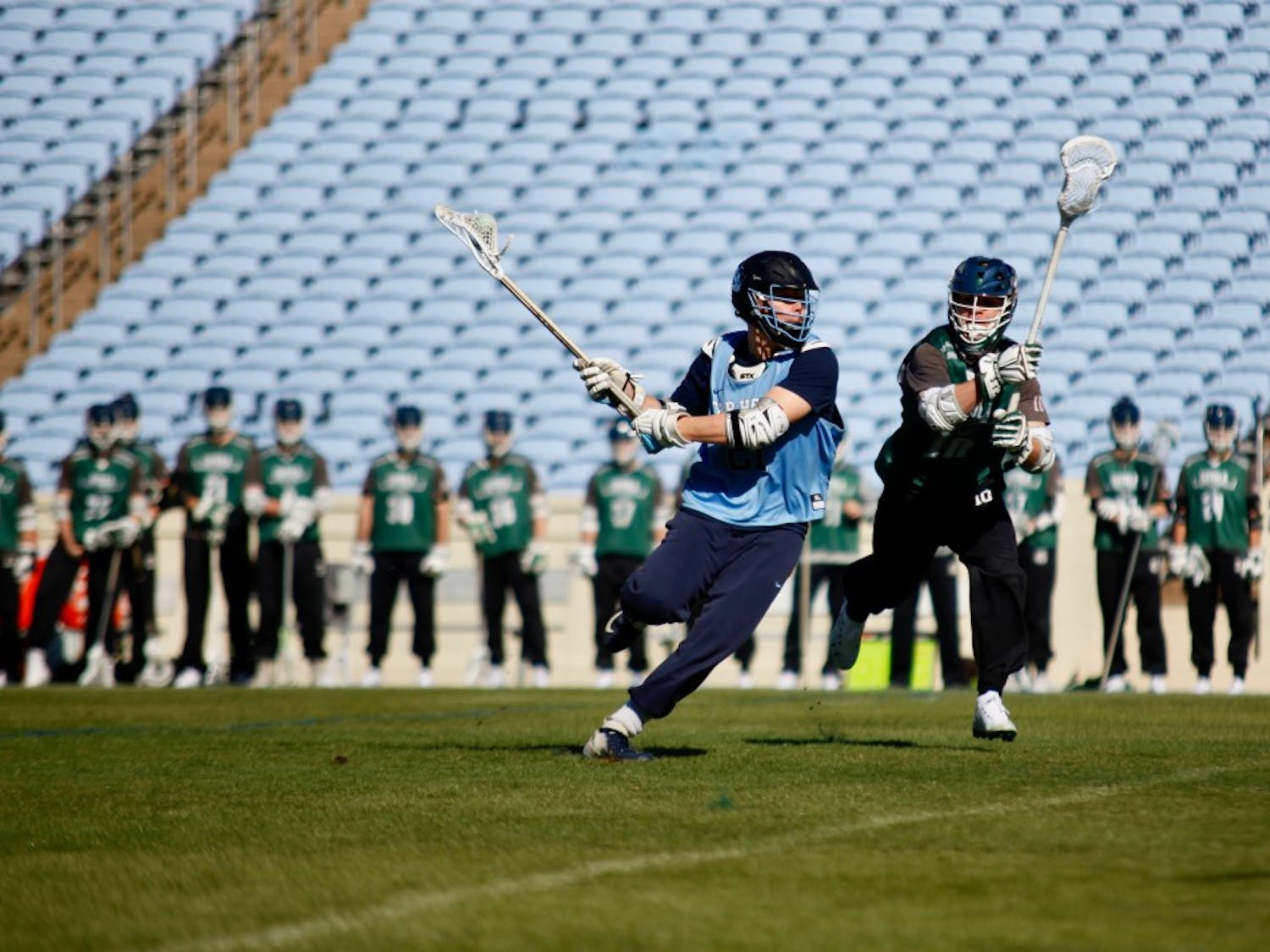 UNC junior midfielder Justin Anderson (21) powers past Loyola midfielder Cole Boland (10) in a scrimmage on Saturday, Jan. 26, 2019 in Kenan Stadium. UNC lost to Loyola with a score of 10-15.