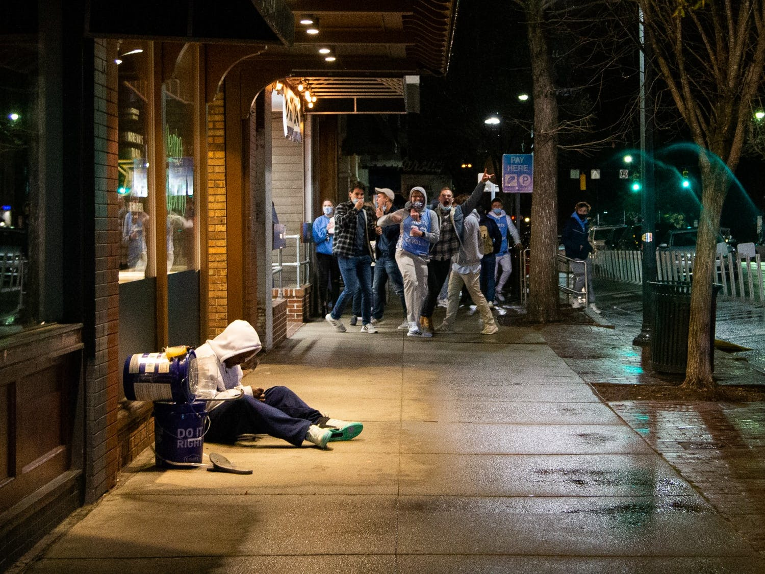Students celebrating UNC's basketball team triumphs over Duke prepare to rush Franklin Street on Saturday, Feb. 6, 2021, while an unhoused man sits under an awning to stay out of the rain.